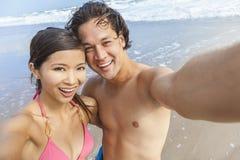 Азиатские пары на пляже принимая фотоснимок Selfie стоковое изображение