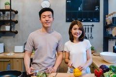 Азиатские пары подготавливают еду совместно Красивые счастливые азиатские человек и женщина варят в кухне Стоковое фото RF