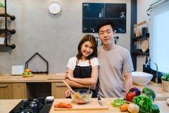 Азиатские пары подготавливают еду совместно Красивые счастливые азиатские человек и женщина варят в кухне Стоковые Изображения RF