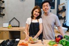 Азиатские пары подготавливают еду совместно Красивые счастливые азиатские человек и женщина варят в кухне Стоковая Фотография