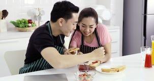 Азиатские пары распространили варенье клубники на хлебе акции видеоматериалы