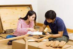 Азиатские пары собирая новую мебель Стоковое фото RF