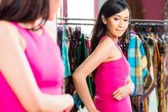 Азиатские покупки женщины в магазине моды стоковое изображение