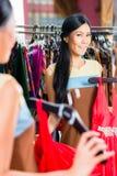 Азиатские покупки женщины в магазине моды стоковые изображения