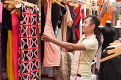 Азиатские покупки человека выбирая портноя магазина платья Стоковые Изображения