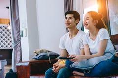 Азиатские предназначенные для подростков пары смотря ТВ совместно счастливо стоковое изображение