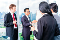 Азиатские предприниматели на flipchart стоковое фото rf