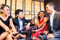 Азиатские друзья выпивая вино в баре Стоковое Изображение