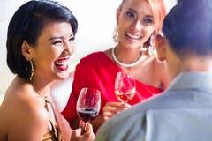 Азиатские друзья выпивая вино в баре Стоковые Фото