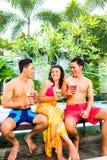 Азиатские друзья выпивая коктеили на бассейне Стоковое фото RF