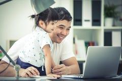 Азиатские семья и маленькая девочка, пока папа работает с тетрадью на w стоковые фото