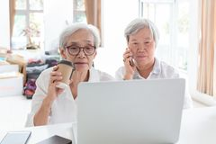 Азиатские старшие женщина и друг с ноутбуком, престарелым наблюдающ что-то интересное пока держащ телефон, говоря стоковая фотография