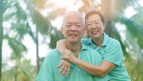 Азиатские старшие пары ослабляя в парке смеясь над в солнечности стоковая фотография rf