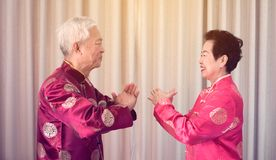 Азиатские старшие пары празднуют китайский Новый Год в красном традиционном костюме стоковое фото
