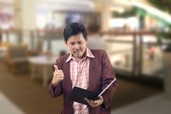 Азиатские таблетка владением бизнесмена и показывать большой палец руки вверх с улыбкой Стоковое Изображение RF
