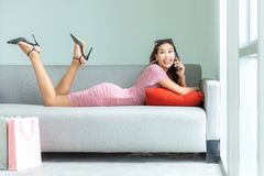 Азиатские усмехаясь покупки женщины настолько счастливые онлайн с ее покупками в случайной одежде с хозяйственными сумками стоковая фотография