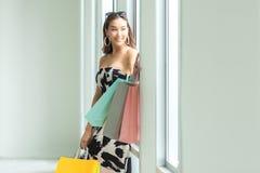 Азиатские усмехаясь покупки женщины настолько счастливые онлайн с ее покупками в случайной одежде с хозяйственными сумками стоковое изображение rf