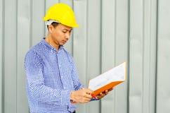 Азиатские файлы удерживания инженер-электрика пока носящ шлем безопасности средств индивидуальной защиты Стоковые Фотографии RF