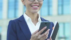 Азиатские хорошие новости чтения коммерсантки от смартфона, счастливого о продвижении сток-видео