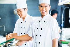 Азиатские шеф-повара варя в ресторане стоковые изображения
