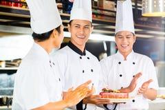 Азиатские шеф-повара варя в ресторане стоковые фото