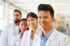 Азиатский ассистент доктора с командой стоковые изображения