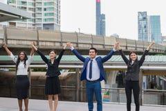 Азиатский бизнесмен, азиатская бизнес-леди и черная бизнес-леди стоя и поднимая вверх 2 руки Стоковые Изображения