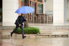 Азиатский бизнесмен бежать в дожде Стоковые Фото