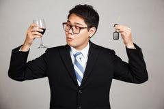 Азиатский бизнесмен выбирает питье или управляет Стоковая Фотография