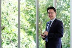 Азиатский бизнесмен держа умный телефон с счастливым усмехаясь st стороны Стоковые Изображения