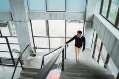 Азиатский бизнесмен идя вверх на лестницы идет к его комнате во вверх стоковые изображения