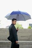 Азиатский бизнесмен идя работать в дожде Стоковая Фотография RF