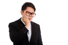Азиатский бизнесмен имеет toothache положить его ладонь на щеку Стоковое Фото
