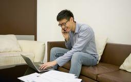 Азиатский бизнесмен используя smartphone в живущей комнате на ноче Стоковое Изображение