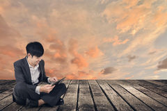 Азиатский бизнесмен используя пусковую площадку и сидит на земле стоковые фото
