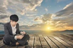Азиатский бизнесмен используя пусковую площадку и сидит на земле стоковые изображения rf