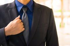 Азиатский бизнесмен касается одной стороне его черного официально костюма Стоковые Фотографии RF