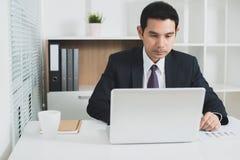 Азиатский бизнесмен концентрируя на использовании портативного компьютера Стоковое Изображение RF