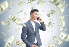 Азиатский бизнесмен на телефоне, дожде доллара Стоковые Изображения
