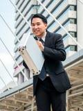 Азиатский бизнесмен обхватывая назад, уважение или извинение Стоковое фото RF