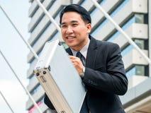 Азиатский бизнесмен обхватывая назад, уважение или извинение Стоковое Изображение