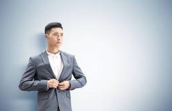 Азиатский бизнесмен около серой стены Стоковые Изображения