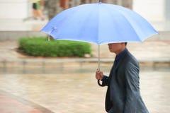 Азиатский бизнесмен под зонтиком Стоковые Изображения RF