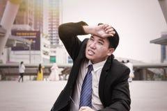 Азиатский бизнесмен принимает eyeglasses утомлянные и посмотренные вверх t Стоковая Фотография