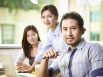 Азиатский бизнесмен работая в офисе стоковое изображение