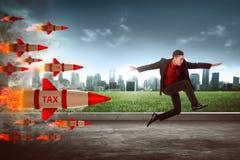 Азиатский бизнесмен скачет от ракеты налога стоковое фото rf