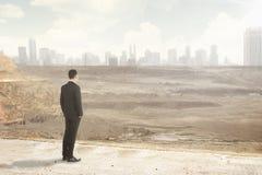 Азиатский бизнесмен смотря разрушенный город стоковые изображения