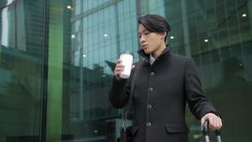 Азиатский бизнесмен стоит около авиапорта и ждать перехода видеоматериал