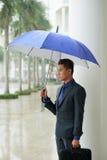 Азиатский бизнесмен стоя в дожде Стоковые Фотографии RF
