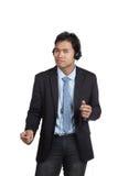 Азиатский бизнесмен счастливый слушает к музыке Стоковое Изображение